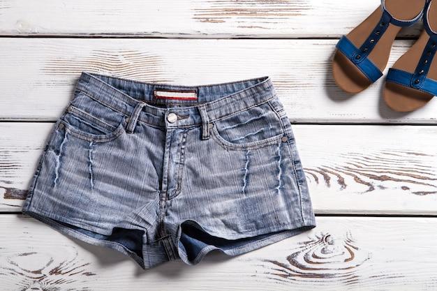 여성용 데님 반바지와 샌들. 선반에 반바지와 신발입니다. 간단한 반바지와 여름 신발. 새 카탈로그의 여름 옷.