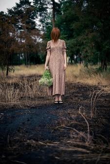 Женщина 40 лет с букетом полевых цветов на выжженной земле, концепция психологического выгорания