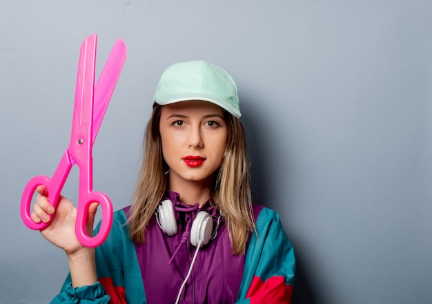 Woman in 90s clothes style with big scissors