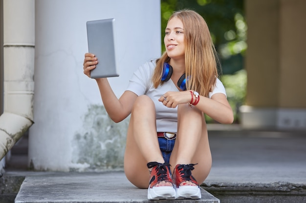 Woman about 20 years old is using tablet pc for chatting with friends while sitting on stairs.