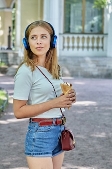 Woman about 25 years old with blond hair and fashionable cloth is eating ice cream outdoor while listening to music with help of earphones.