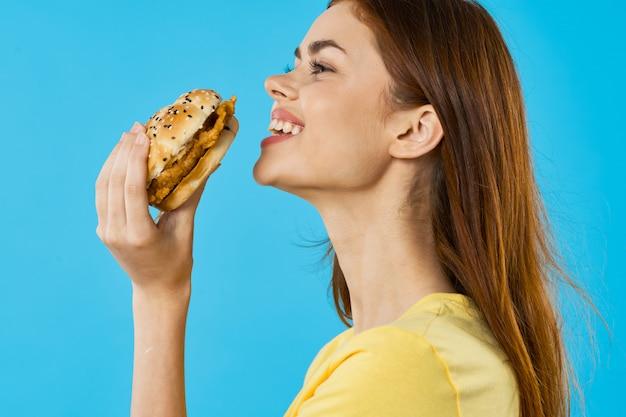 Женщина собирается съесть бургер