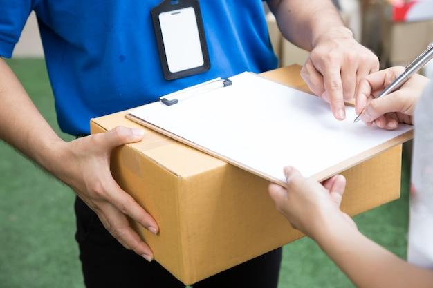배달원에서 골 판지 상자 배달을 수락하는 여자.