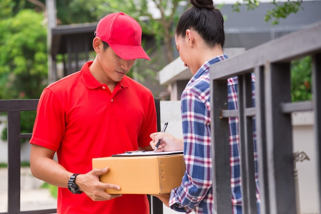 Woman accepting a delivery of boxes from delivery service courier.