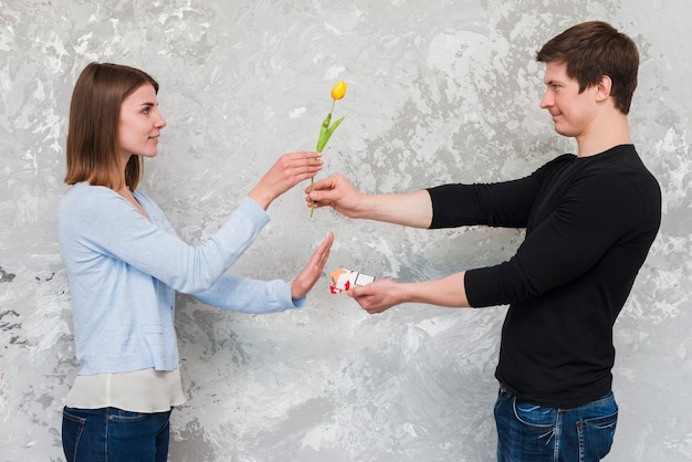 Woman accepting yellow tulip flower and no to cigarette packet offering by handsome man