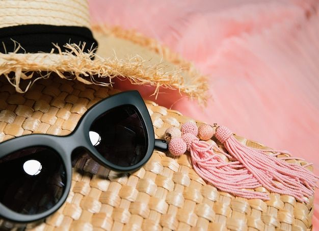 Woman accessories. earrings, fragment of a straw bag, straw hat, black trendy sunglasses