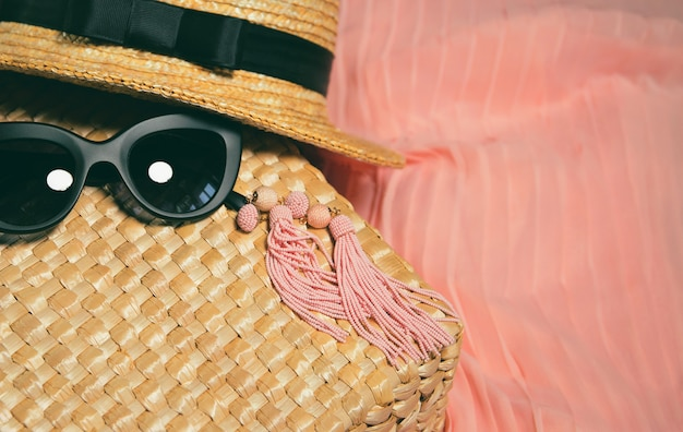 Woman accessories. fragment of a straw bag, earrings, straw hat, black trendy sunglasses