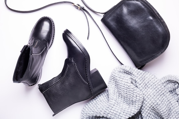 Woman accessory. black stylish boots, black luxury leather bag, gray scarf. top view. flat lay.