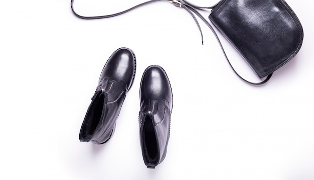 Woman accessory. black stylish boots, black luxury leather bag. top view. flat lay.