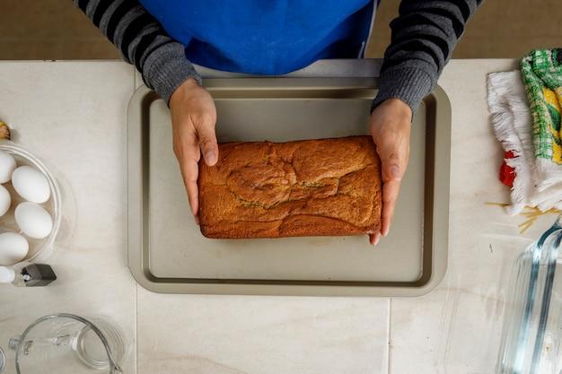 Женщина кладет руками свежеиспеченный блин концепция домашней выпечки