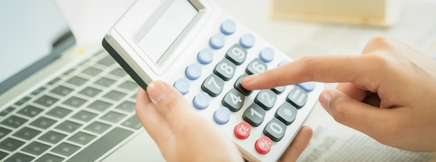 Woman accountant or bank worker uses calculator.