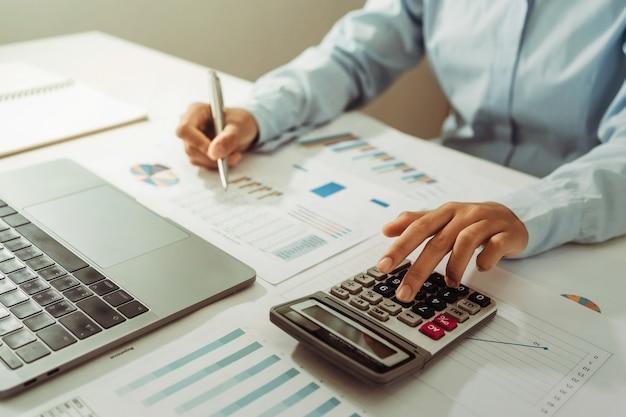 女性会計士は、オフィスの机の上にペンを持って電卓とコンピューターを使用します。財務および会計の概念