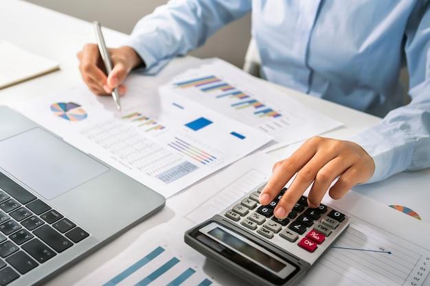 여성 회계사 사무실에서 책상에 펜을 들고 계산기와 컴퓨터를 사용합니다. 재무 및 회계 개념