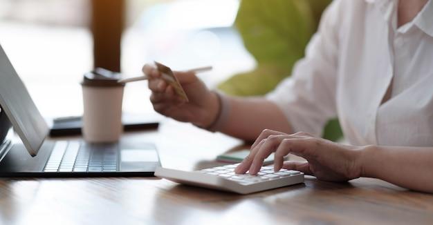 사무실에서 계산기를 사용하고 신용 카드, 손 클로즈업, 파노라마 배너를 들고 일하는 여성 회계사. 온라인 쇼핑 개념입니다.