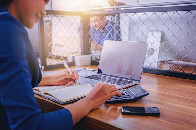 Женщина бухгалтер работает с помощью калькулятора для расчета финансового отчета на рабочем месте.