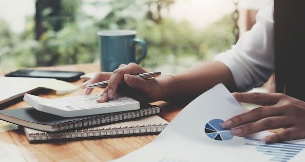Бухгалтер женщина, работающая с компьютером и калькулятором для деловых и финансовых расходов
