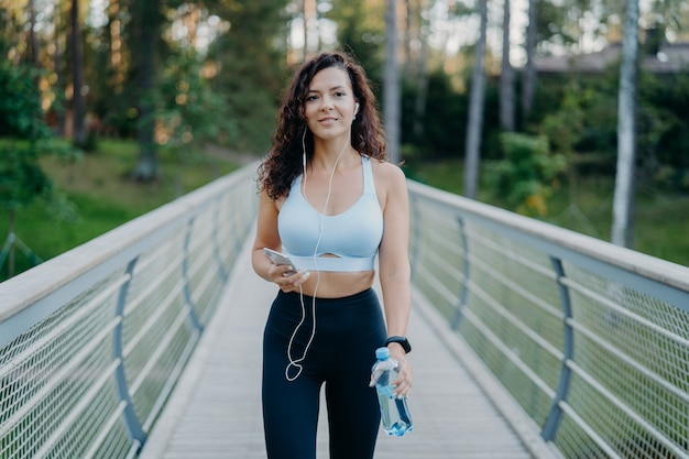Woman in active wear goes jogging near forest, enjoys listening music in earphones