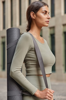 La donna in activewear porta il karemat arrotolato focalizzato sulla distanza che va ad avere un allenamento fitness in pose all'aperto su sfocato