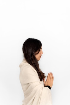 Woman in activewear and shawl meditating with namaste hands in white background during yoga session