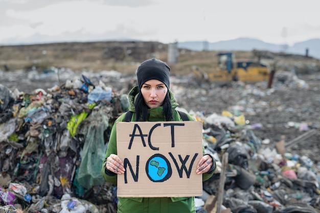 Активист женщина держит плакат на свалке, концепция загрязнения окружающей среды.