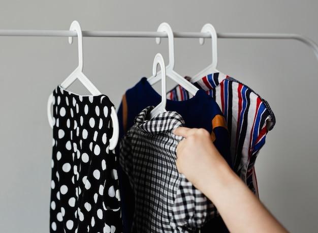 Donna che aggiunge vestiti alla cremagliera dei vestiti di vendita