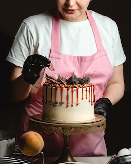 Woman adding fig piece on classic cake decorated with figs and syrup