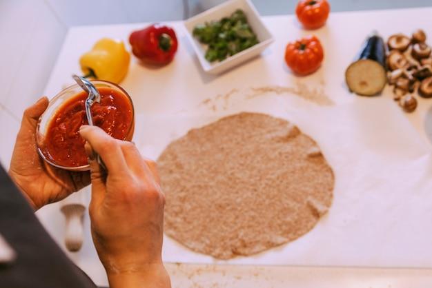 ピザにヘルシーな食材を加える女性。自家製のコンセプト。