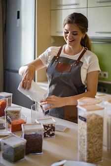 Женщина добавляет здоровую гороховую пасту в прозрачную коробку для хранения на кухне