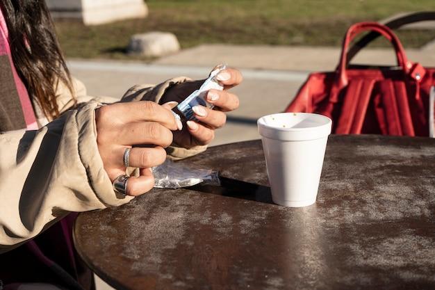 晴れた日にカフェのテラスでコーヒーに砂糖を加える女性。リラクゼーションと自由時間の概念。