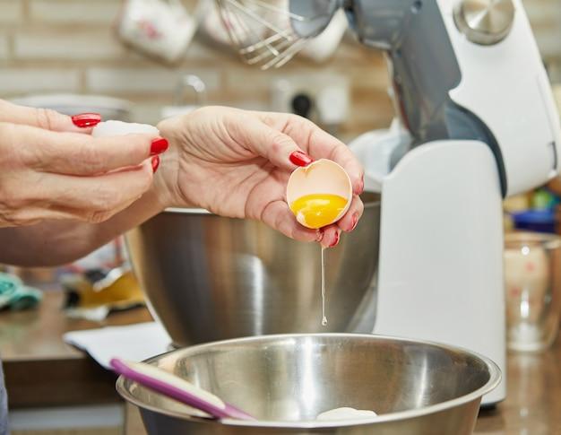 여성이 반죽에 계란을 추가하여 인터넷에서 제공하는 단계별 조리법 인 풍미가있는 치즈 파이를 만듭니다.