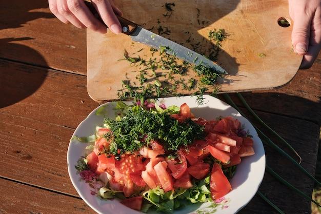 여자는 야채 샐러드에 딜을 추가합니다