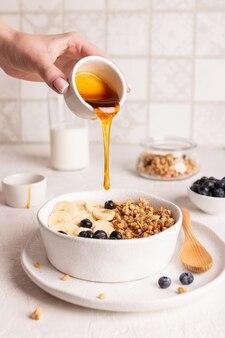 女性がグラノーラに蜂蜜を加え、ミューズリーとフルーツを使ったヘルシーな朝食