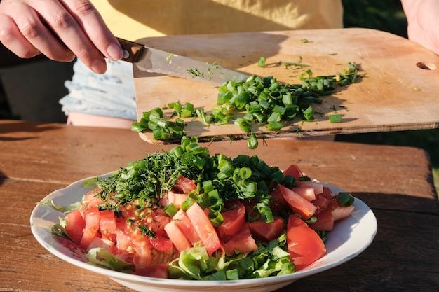 여자는 야채 샐러드에 양파를 추가합니다