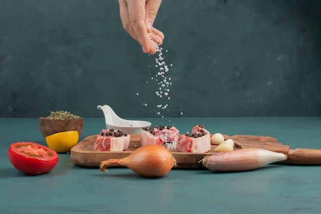 여자는 파란색 테이블에 생 쌀된 고기 조각에 소금을 추가합니다.