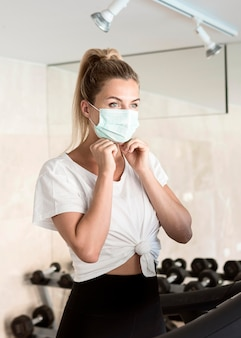 ジムにいる間に彼女の医療マスクを調整する女性
