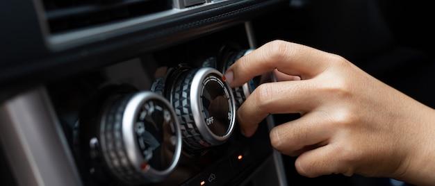 도로에서 운전하는 동안 실내 온도를 조절하는 여성