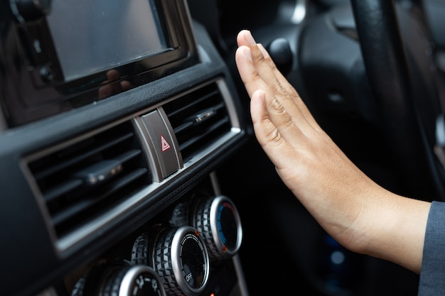 그녀의 차 안에서 냉각을 조정하는 여자