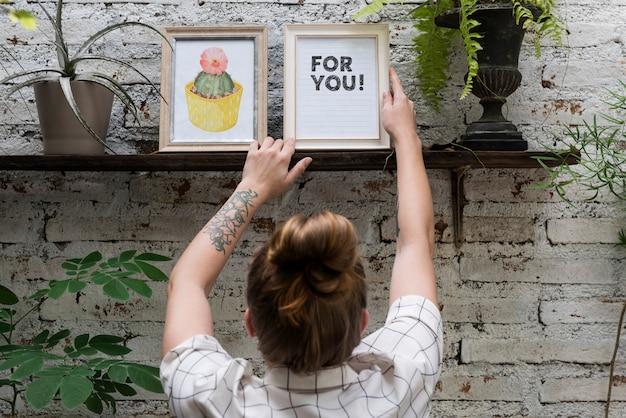 Woman adjusting for you photo frame on shelf