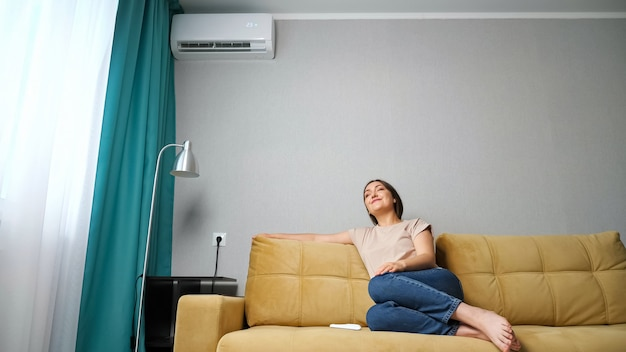 Woman adjusts the air conditioner while sitting on the couch,