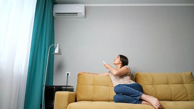 Женщина регулирует кондиционер, сидя на диване.