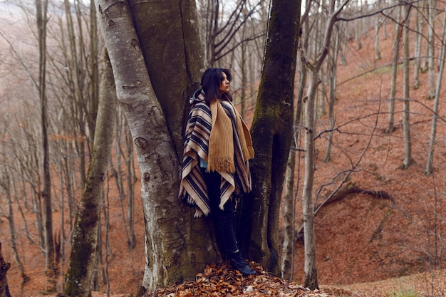 A woman admires the autumn views on a cold day into the wood