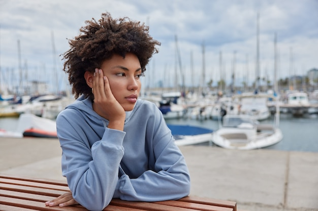 Woman admires yachts and calm sea water spends free time on harbor pier dressed in hoodie dreams about summer journey on vacation walks outdor after quarantine