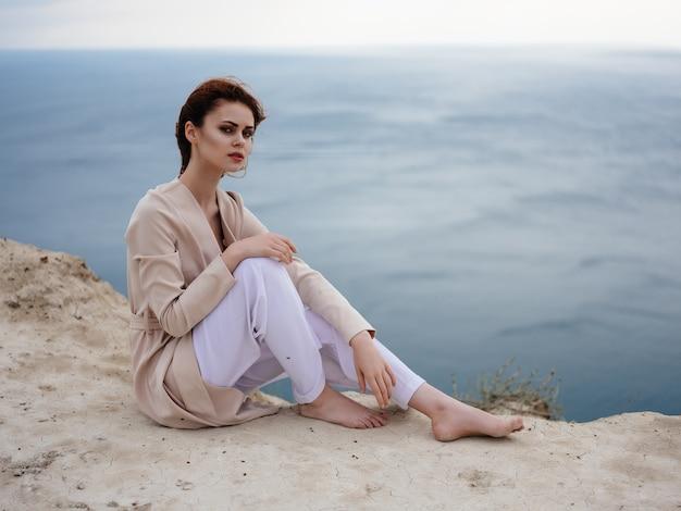 海の岩石ロマンスリラクゼーションを賞賛する女性