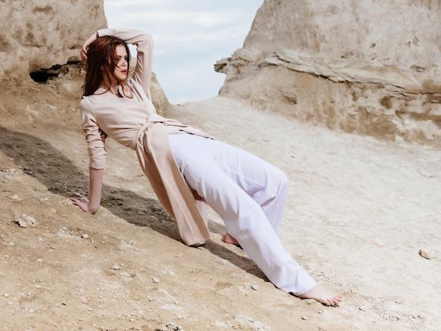 海の岩石ロマンスリラクゼーションを賞賛する女性 Premium写真