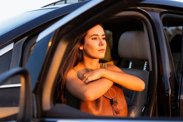 車の座席から夕日を眺める女性