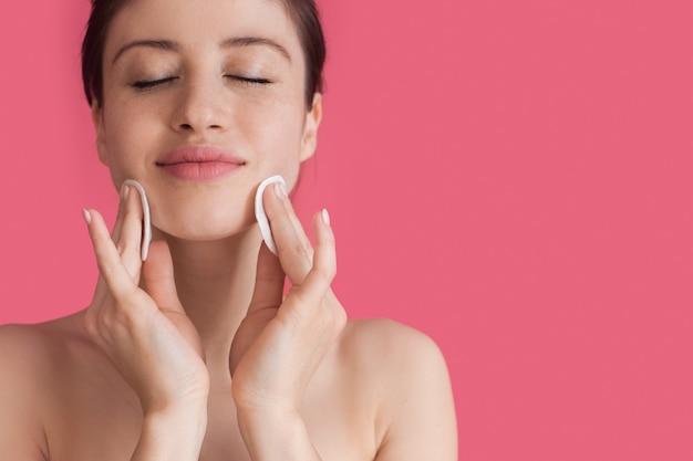 綿のディスクで顔を掃除し、目を閉じて笑顔でピンクの壁に何かを宣伝する女性