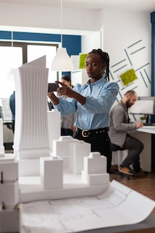 Woman of african american ethnicity working as architect with building plans