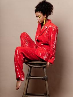 Женщина афроамериканец в блестящей праздничной модной одежды на цветном пространстве позирует