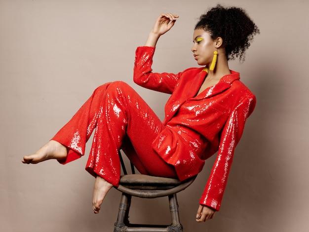着色された表面のポーズに光沢のあるお祭りファッション服の女性アフリカ系アメリカ人