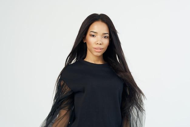 女性のアフリカの外観と長い黒髪の化粧品の明るい背景
